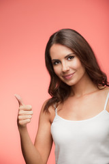 Smiling woman showing thumb up gesture, over red