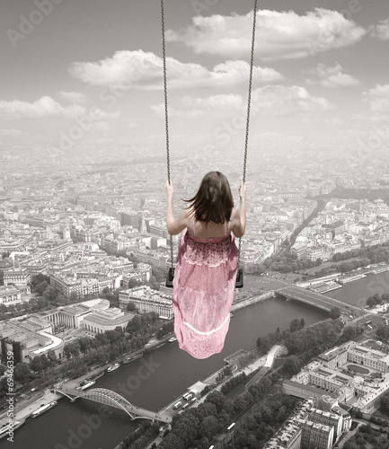 Young woman on a swing on the Paris town backround. Surrealism c