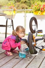 KLeines Mädchen reinigt sein Fahrrad