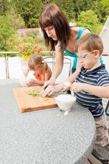 Mutter bereitet mit ihren Kindern das Essen zu