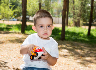 Cute little child boy  plays with toy car in park on nature