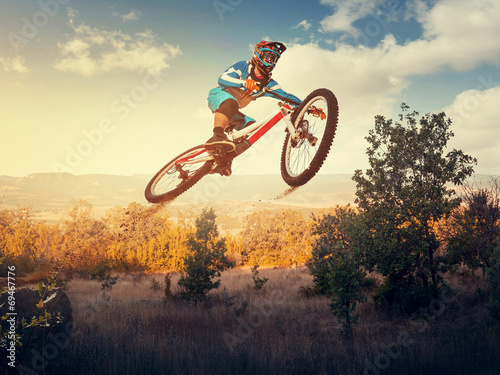 canvas print picture Man high jump on a mountain bike. Downhill cycling.