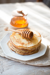 Pancakes with honey on the kitchen table