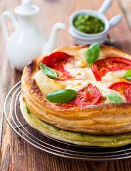 pie of puff pastry with tomato, mozzarella and pesto sauce