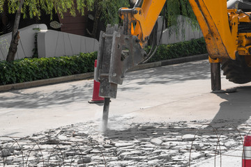 Excavator breaking and drilling concrete road for repairing