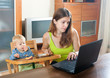 Woman working with laptop and baby