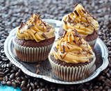 Fototapety Muffins with caramel cream on coffee beans  background