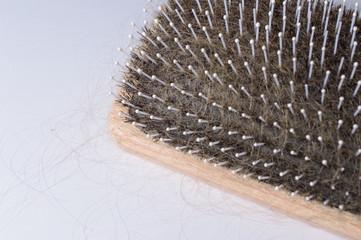 Haarbürste voller Haare wegen Alopezie heller Hintergrund