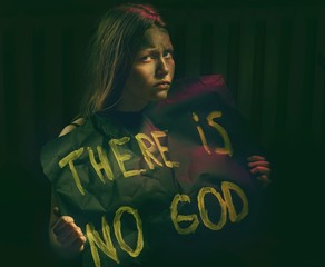Teen girl with dirty face holding banner with a text .Atheist