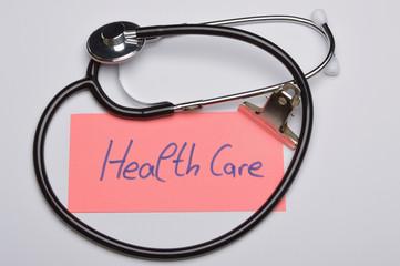 Notizzettel mit Aufschrift Health Care neben Stethoskop
