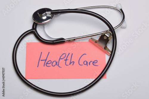 canvas print picture Notizzettel mit Aufschrift Health Care neben Stethoskop