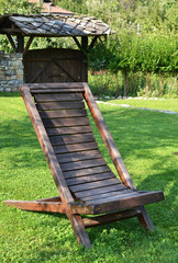 Chaise longue from wood on meadow