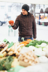 Young man buying fresh vegetables at farmer's market