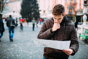 Man looking at city map on a trip. Looking for directions.