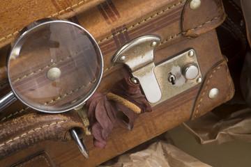 Valigia vecchia e lente d'ingrandimento