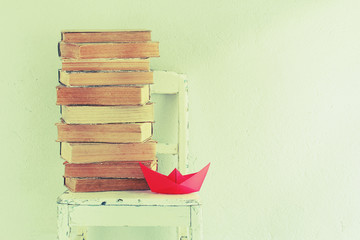 Background with old books, chair and red paper boat