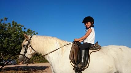 Niña montada en caballo blanco