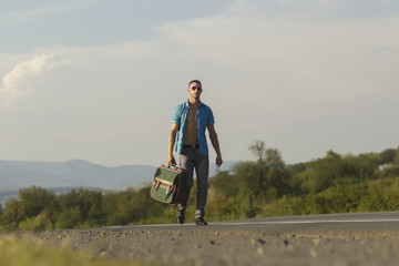 Handsome guy on the road with bag against the sky and mountains