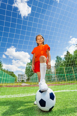Girl with leg on football in front of woodwork