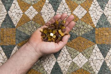 Mosaico e mani con tessere