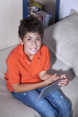 Happy young boy is sitting with his tablet PC