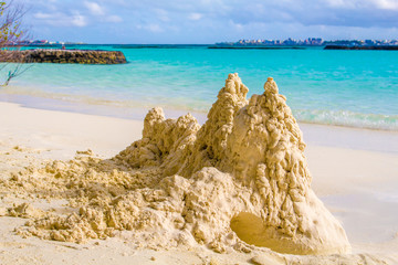 Sand castle on the beach in front of ocean with Male in the back