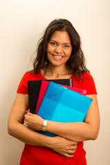 beautiful latina holding folders.