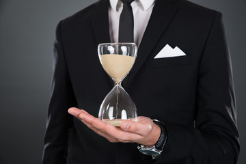 Midsection Of Businessman Holding Hourglass