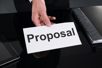 Businessman Holding Proposal Sign At Desk