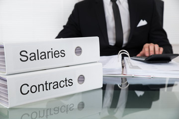 Businessman Calculating Salaries And Contracts