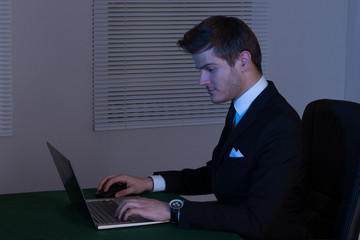 Businessman Working Late On Laptop At Desk