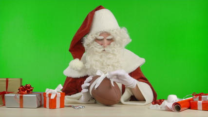 Santa Claus is Tying a Bow on a Football