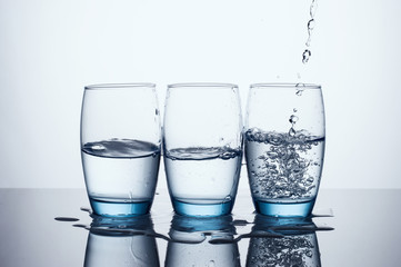 Pouring Water In Three Water Glasses