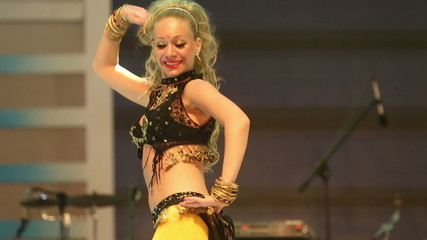 girl dancing on stage in a yellow black national Indian