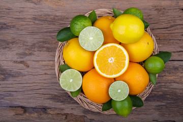 Mix of fresh citrus fruits in basket on  wood