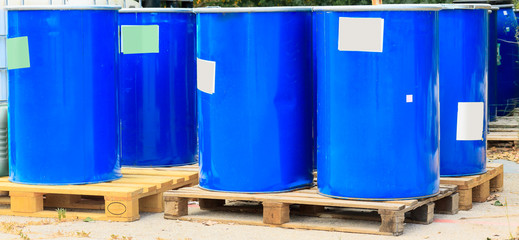 Some blue barrels on wooden pallets