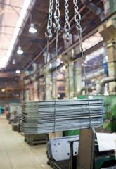 Workshop crane transporting metal sheets cargo