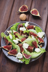Figs, mozzarella and walnuts salad over brown wooden background