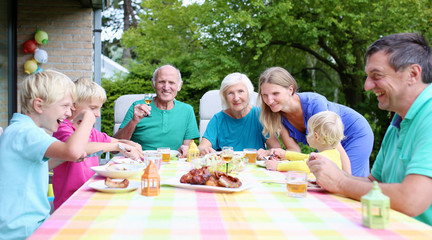 Happy family with kids and grandparents having lunch together