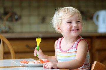 Happy little girl eating healthy salad in the kitchen