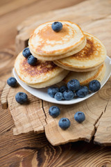 Pancakes with fresh blueberries over rustic wooden background