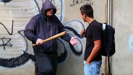 Man with a baseball bat against teenager with a backpack