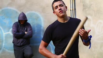 Aggressive teenager with a baseball bat with man behind