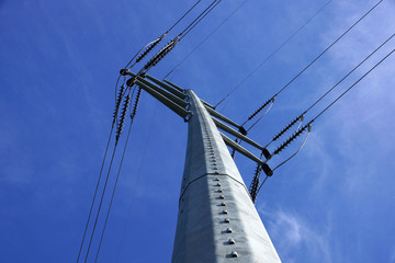 High Voltage Power Lines intersect at a large metal Utility pole