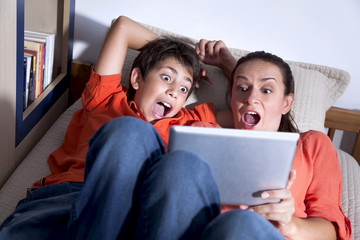 Surprised young boy and his mother are playing with tablet PC