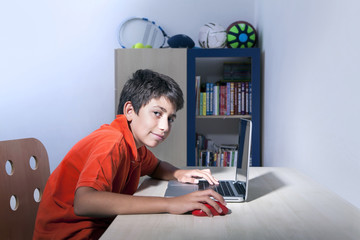 Young boy is looking to us when he is on computer