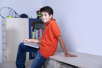 Happy young boy is sitting with his computer