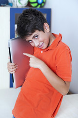 Happy young boy is showing his computer