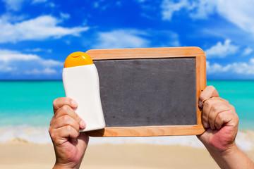 Sonnenmilch und leere Schiefertafel am Meer
