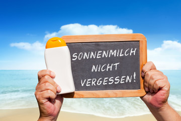 Hände halten Tafel mit Text: Sonnenmilch nicht vergessen